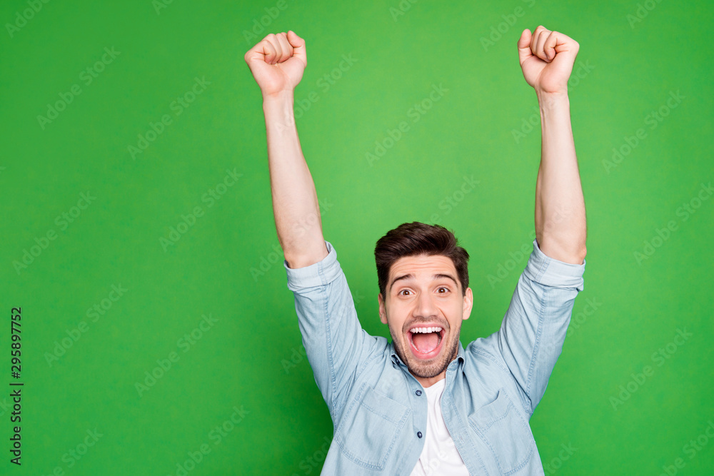 Fototapeta Photo of amazing crazy guy yelling loudly celebrating favorite football team victory raise fists up wear casual denim shirt isolated green color background