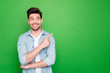 Leinwandbild Motiv Photo of amazing salesman guy in excited mood indicating finger to empty space advising cool shopping prices wear casual denim shirt isolated green color background