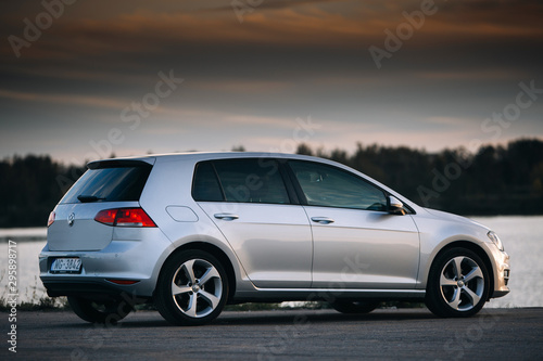 Fototapeta Volkswagen Golf MK7 near river at the sunset