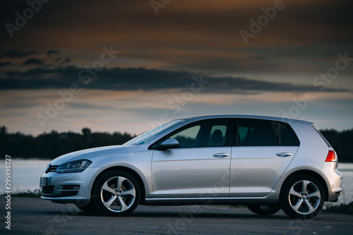 Fotografia, Obraz Volkswagen Golf MK7 near river at the sunset