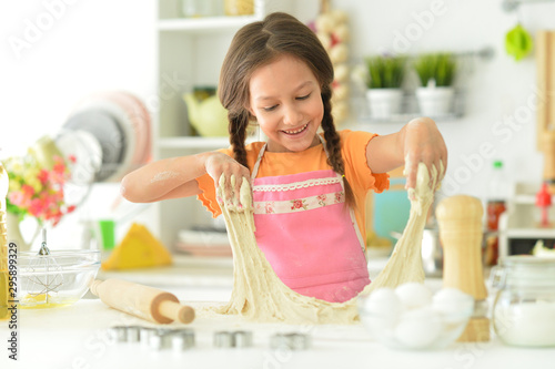 Fotomural  Portrait of a young girl baking in the kitchen