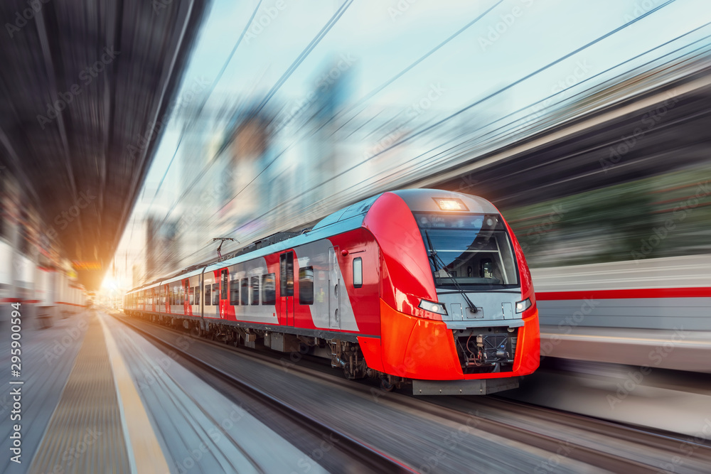 Fototapety, obrazy: Electric passenger train drives at high speed among urban landscape.