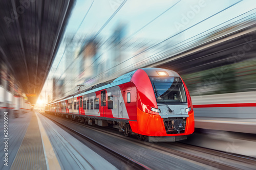 Electric passenger train drives at high speed among urban landscape.
