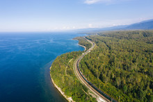 Aerial View Of A Freight Train On The Railroad Of Trans-Siberian Railway On The Shore Of Baikal Lake With Green Forest Trees In A Sunny Summer Day. East Siberian Railway In Buryatia, Siberia, Russia