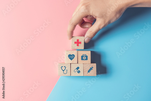 Fotomural  Health Insurance Concept, Hand of man arranging wood cube stacking with icon healthcare medical on pastel blue and pink background, copy space