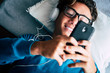 canvas print picture - Close up of young phone addicted teenager using mobile cellular lay down on the sofa at home - happy technology millennal people with internet connection device  listening music with heaphones