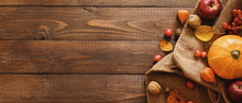 Harvest Or Thanksgiving Background With Pumpkins, Blanket, Dried Fall Leaves, Apples, Red Berries, Walnuts On Wooden Table. Flat Lay Composition, Top View, Copy Space