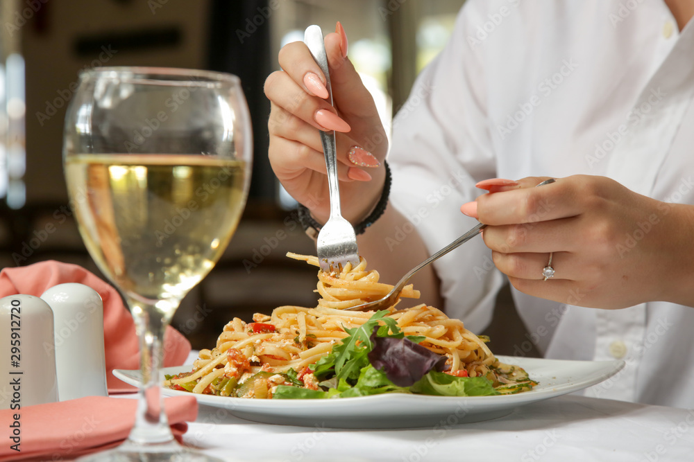 Fototapety, obrazy: Young woman having spaghetti and a glass of white wine in the restaurant