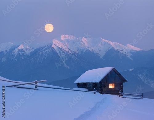 Christmas landscape with a snowy house in the mountains on a moonlit night Canvas-taulu