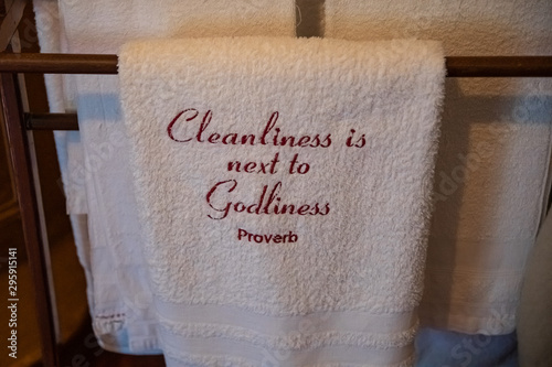 White towel with Cleanliness is next to Godliness proverb embroidered on it Canvas Print