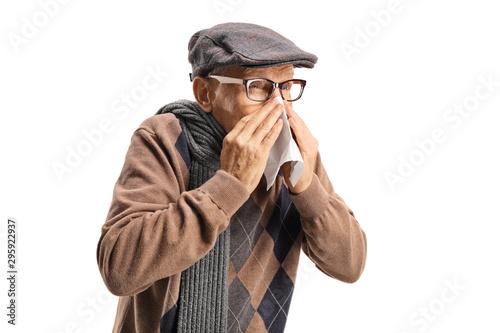 Senior man sneezing and wiping nose