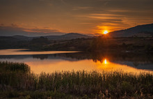 Natural Scenic Of A Golden Sunset Just Above A Distant Mountain Range With Forest Hills Around A Calm Watered Lake With Still Water And Nice Reflections, Some Grass In The Foreground And Darkening Sky