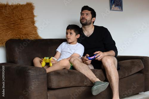 Padre latino juega con su hijo en sofá Canvas Print