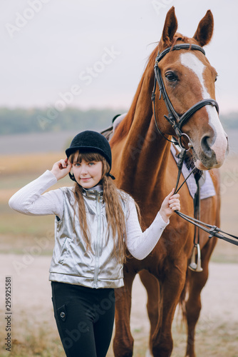 Fototapeta First lessons of horseback riding. Young beautiful girl riding a horse in a field. obraz