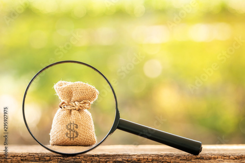 Magnifying glass with searching for money bag put on the wood on bokeh background, Loan and find for business investment fund  in the future concept Fototapete