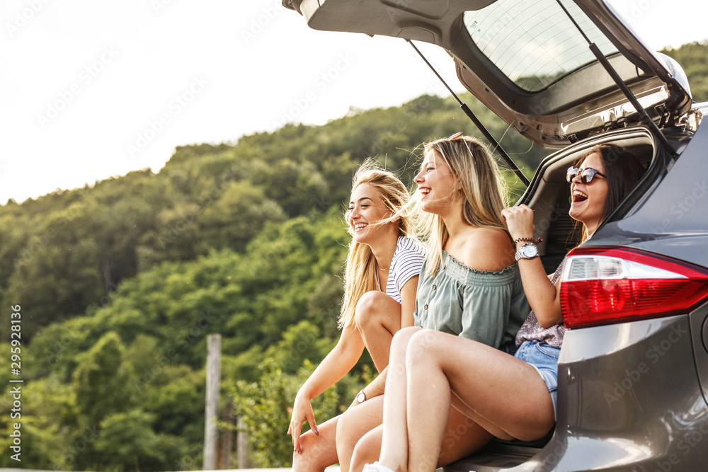 Fototapety, obrazy: Group of female best friends on travel . They sitting on car trunk and relaxing after long journey.