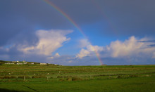 Colourful Rainbow Arc In Irish Landscape Landing On A  Rocky Outcrop In Middle Of Field