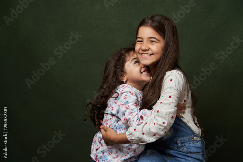 Fotografie, Tablou Two sisters portrait on green background with copy space