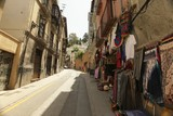 Fototapeta Uliczki - Low angle shot of a narrow street with clothing being sold on the sidewalk in Granada, Spain