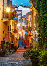 Bellagio Village At Lake Como Near Milan Italy, Region Lombardy. Famous Street With Paving Stones Stairs And Cosy Restaurants During Sunrise With Glowing Lanterns And Green Plants On Old Houses Walls.