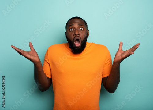 Amazed and shocked expression of a boy over cyan background Wallpaper Mural