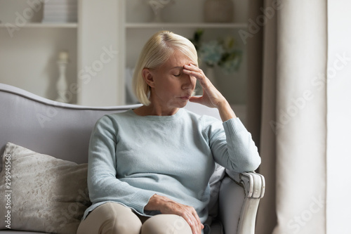 Exhausted mature lady suffering from head ache at home. Canvas Print