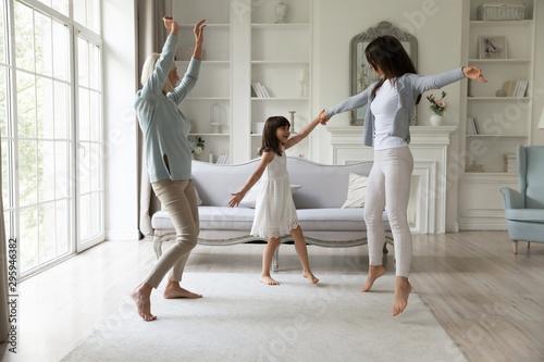 Fotografía  Full length happy 3 generations family having fun together in living room