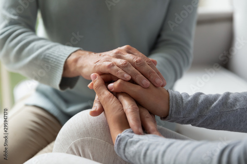 Carta da parati Close up young lady and middle aged woman connecting hands.