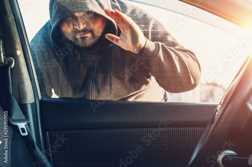 Fotografía  Criminal person in hood looks inside car through glass or window, Robber or car