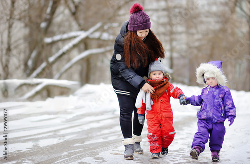Young asian woman helping caucasian toddler boy anf girl with their winter cloth Wallpaper Mural