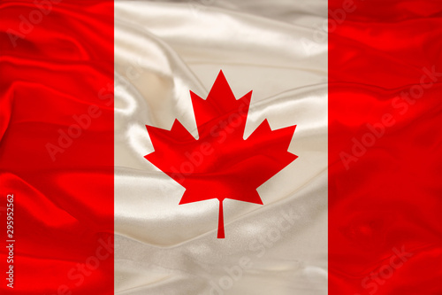 photo of the beautiful colored national flag of the modern state of Canada on textured fabric, concept of tourism, emigration, economics and politics, closeup