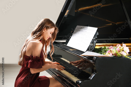 Young woman playing grand piano at the concert Fotobehang