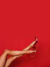 Beautiful Long Legs In Red High Heels With A Copy Space In The Background.