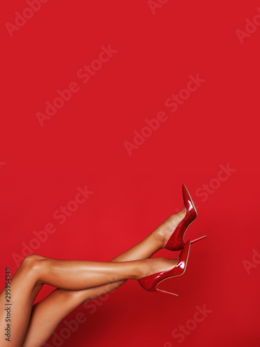Valokuva Beautiful long legs in red high heels with a copy space in the background