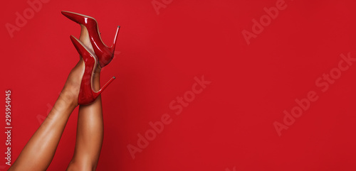 Fototapeta Beautiful long legs in red high heels with a copy space in the background