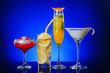 Leinwandbild Motiv Different tasty cocktails on dark color background