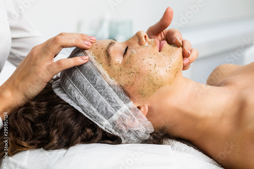 Fotografía Beautiful woman receiving facial mask with rejuvenating effects in spa beauty salon