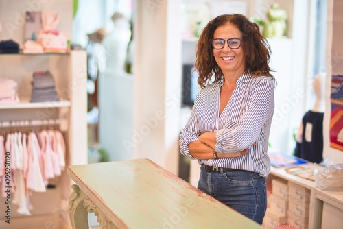 Middle age beautiful clothes shop owner woman smiling happy and confident waitin Fotobehang