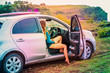 canvas print picture - A beautiful surfer girl sitting in the car watching tidal waves at sunset