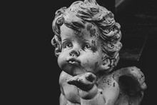 Black And White Image Of Putto Or Child Angel Figurine With Blown Kiss Gesture, Copy Space For Text, Horizontal