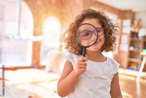 Obraz Beautiful toddler standing  wearing glasses using loupe at kindergarten - fototapety do salonu