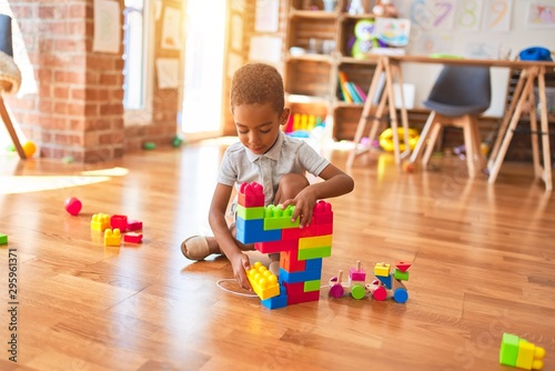 Beautiful african american toddler playing with building blocks smiling at kinde Canvas Print