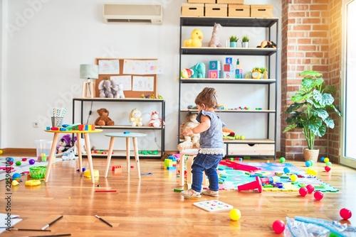 Pinturas sobre lienzo  Beautiful toddler standing around lots of toys at kindergarten