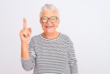 Senior Grey-haired Woman Wearing Striped Navy T-shirt Glasses Over Isolated White Background Showing And Pointing Up With Finger Number One While Smiling Confident And Happy.