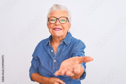 Senior grey-haired woman wearing denim shirt and glasses over isolated white background smiling cheerful offering palm hand giving assistance and acceptance Wallpaper Mural