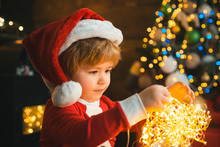 Child With Garland Lights At Christmas Tree And Fireplace On Xmas Eve. It Is Miracle. Family With Kids Celebrating Christmas At Home. Boy Cute Child Cheerful Mood Play Near Christmas Tree.