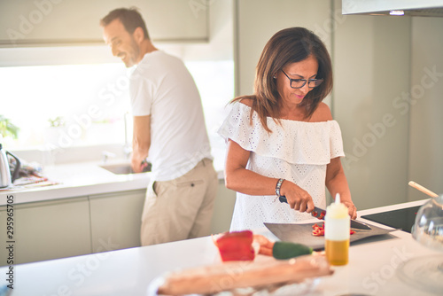 Fotografie, Obraz  Middle age beautiful couple cooking together on the kitchen