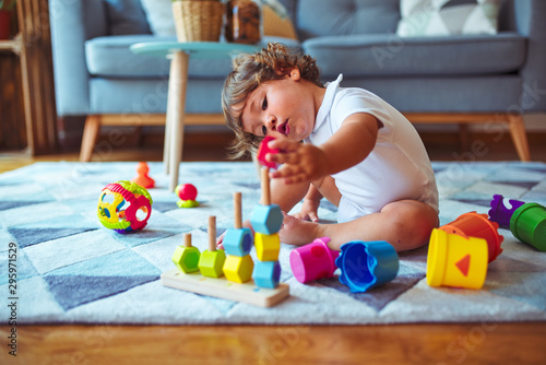 Fototapeta Beautiful toddler child girl playing with toys on the carpet