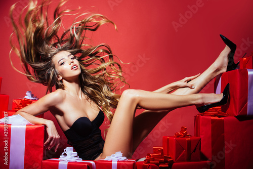 Luxurious long hair. Fashion hairstyle. Hair model. Girl in sexy lingerie. Happy Day. Celebration and party. Sexy blonde woman with gift.
