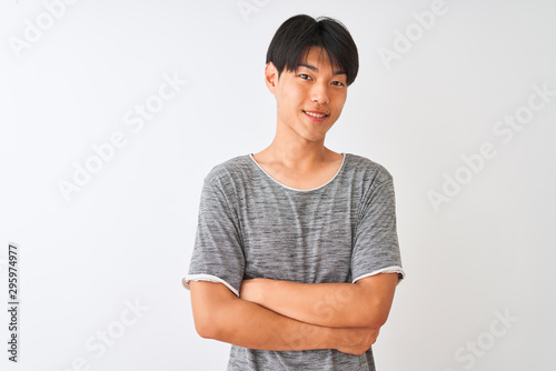 Fotografia  Young chinese man wearing casual t-shirt standing over isolated white background happy face smiling with crossed arms looking at the camera